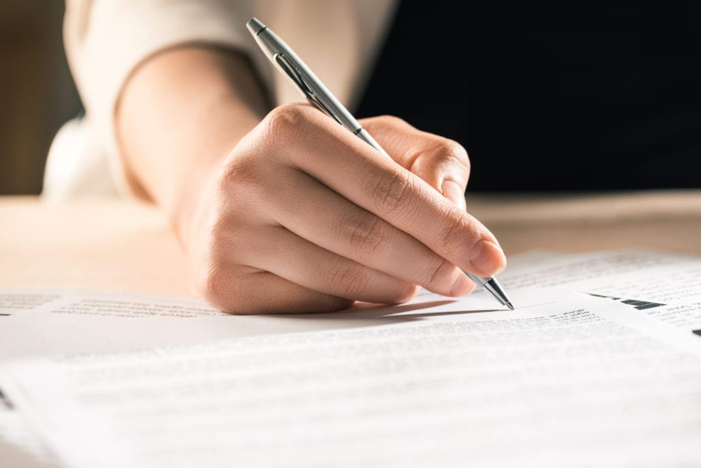 A person signs an estate planning document