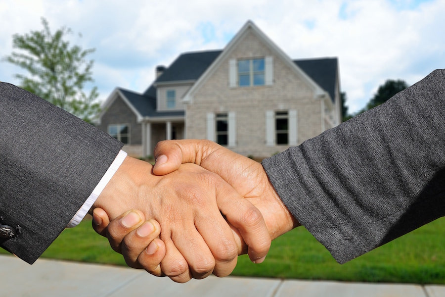 Two people shake hands in front of a property. Properties can be assets in both wills and trusts.