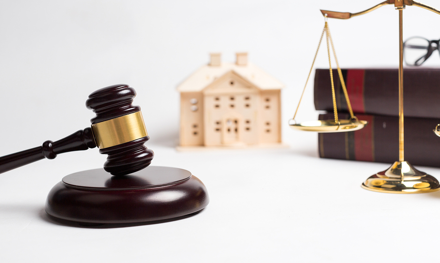 A gavel, scales and books sit in front of a replica of an estate representing the legal process for appointing an executor of estate.