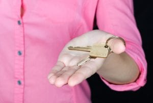 A person in a pink button down holds the keys to a home they acquired through probate real estate.