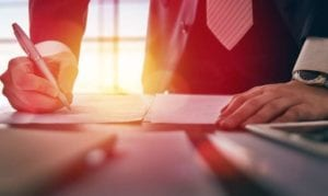 A probate real estate attorney signs a document as orange sunlight gleams through a window