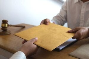 A chapter 7 bankruptcy attorney hands a large manila envelope to a client