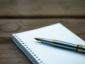 A pad of paper with a silver pen sitting on top as the owner learns how to make a will