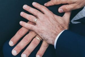 A spouse holds hand with their partner as they both learn how to set up a trust