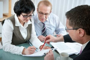 A couple signs paperwork with an attorney as they discuss debt consolidation vs. bankruptcy