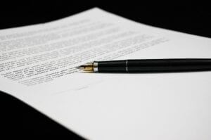 paperwork for making an estate plan sits on a table with a black pen