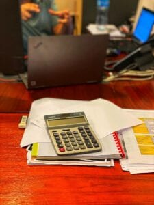 A calculator on a red wood desk with piles of paperwork in bankruptcy lawyers' firm