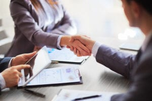 Two creditors shake hands with a clients as they negotiate how to pay off unsecured debt