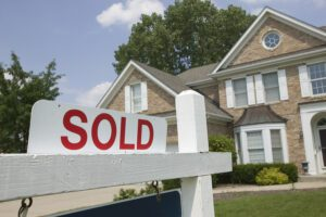 A sold sign in front of a house due to real estate investing
