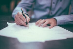 a lawyer in a blue button down explains what is probate as he signs documents